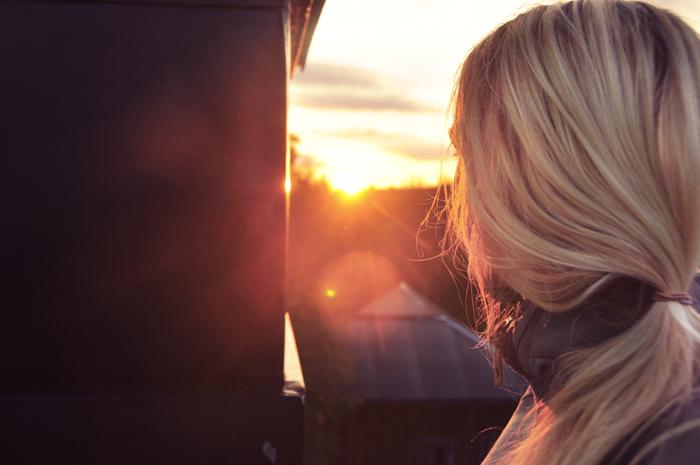 Uppe på taket intill skorstenen och tittar på solnedgången.