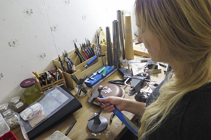 """I verkstaden och jobbar. Just här håller jag på att tillverka """"tags"""", som sätts på många av smyckena som ett bevis att det är tillverkat av oss och är av äkta silver. Dem bankar jag ut från en silverplåt, borrar, slipar, stämplar och löder fast i ringar."""