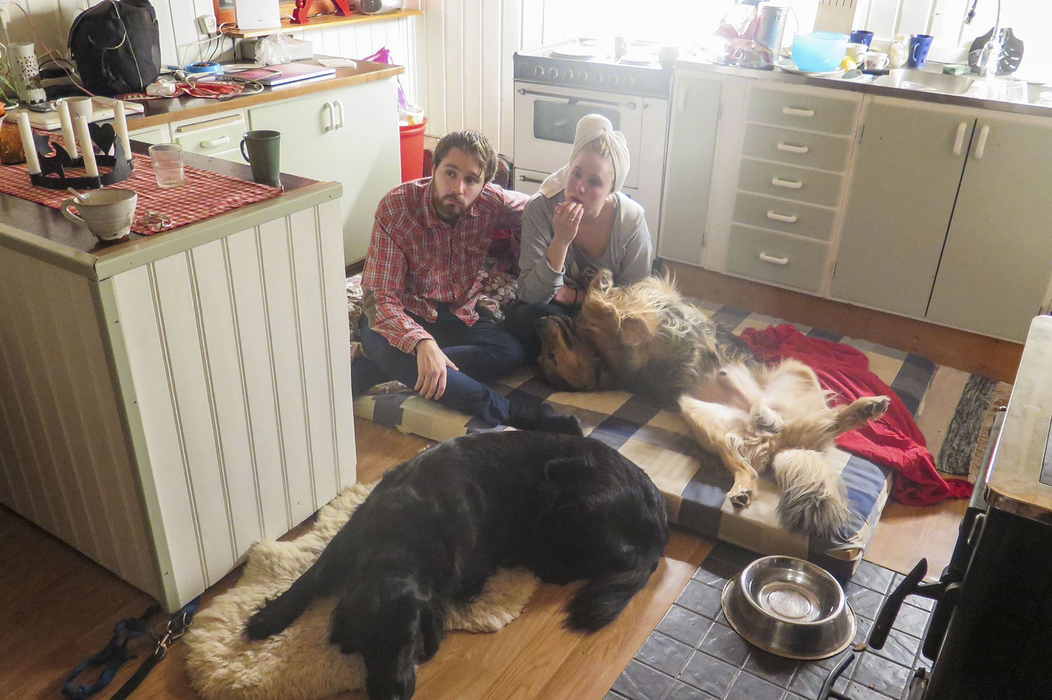 Min lillebror Filip och hans flickvän Johanna på en madrass i mitt kök, med hundarna tätt intill.